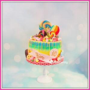 taart in regenboogkleuren en met veel snoep