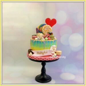 driptaart in regenboogkleuren met snoep en macaron